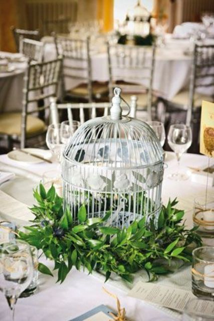 a birdcage surrounded with lush foliage for a chic and non-typical wedding centerpiece