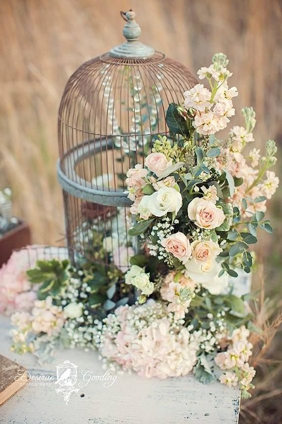 a birdcage with crystals inside and lush pink florals and greenery attached outside