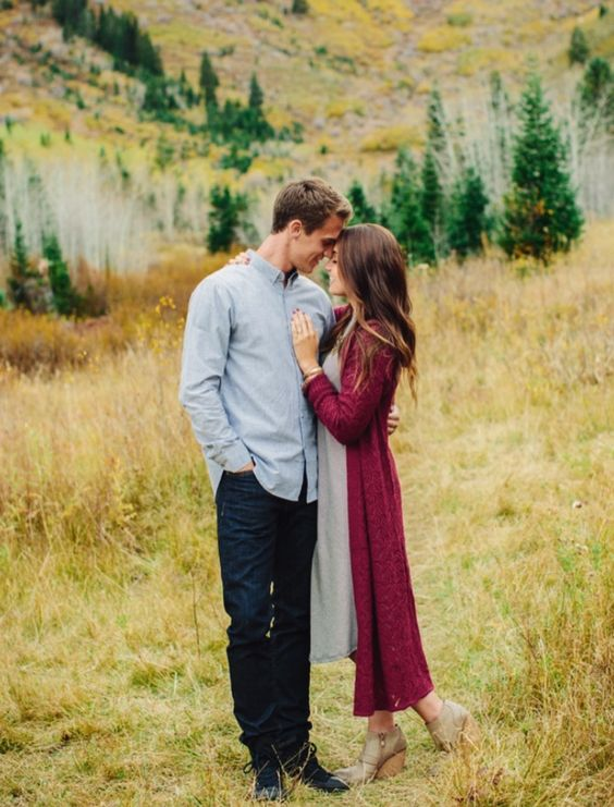 the bride-to-be is wearing a grey midi dress and a long plum-colored cardigan and greey booties to embrace the fall
