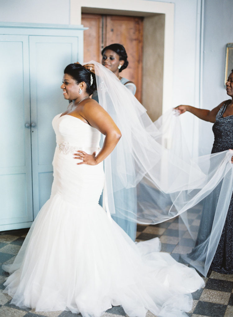 The bride chose a strapless mermaid wedding gown with a train, statement earrings and a veil