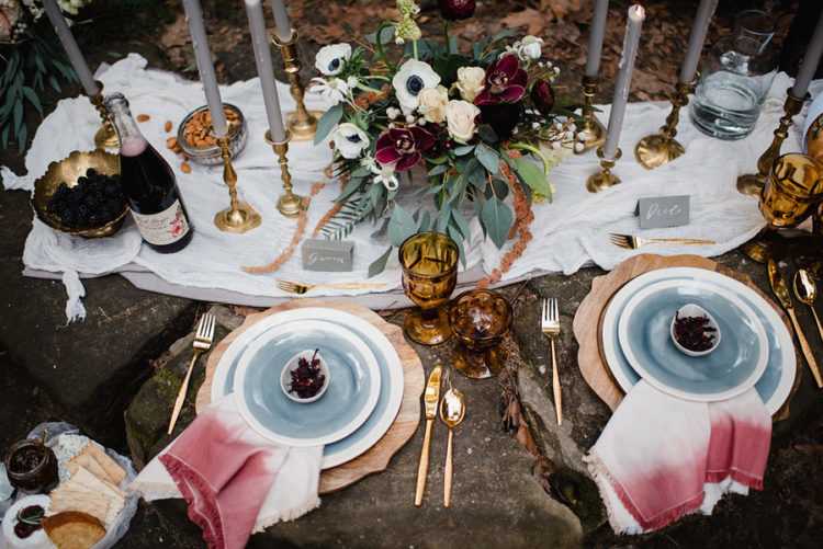 The picnic tablescape was done with blue dinnerware, ombre pink napkins, grey candles, amber and gold details