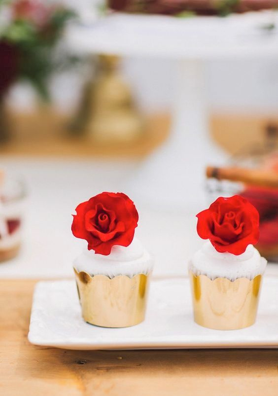 creamy cupcakes topped with red roses and in gold foil