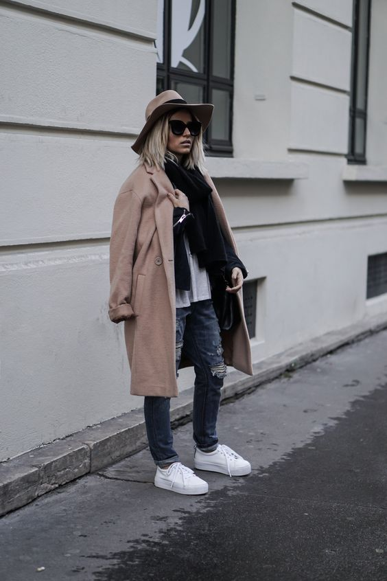 ripped jeans, white sneakers, a neutral top and a black scarf, a camel coat and a camel hat