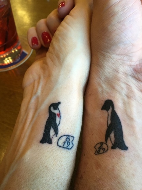 Matching penguin tattoos on the wrists