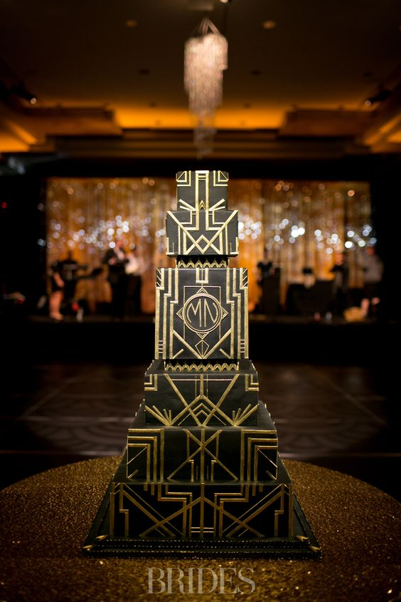 a square multi-layer black and gold wedding cake with geometric decor