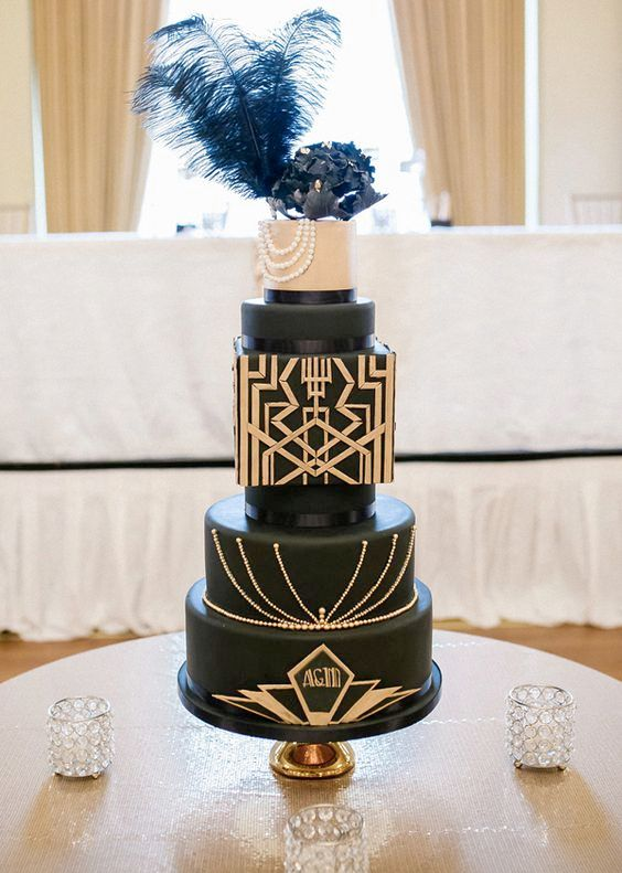 a black wedding cake with differently shaped layers, gold geo decor, a black sugar flower and black feathers
