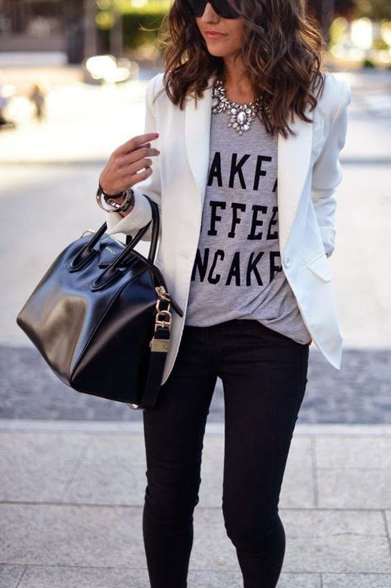 black jeans, a white blazer, a printed grey t-shirt, a statement necklace and a black bag