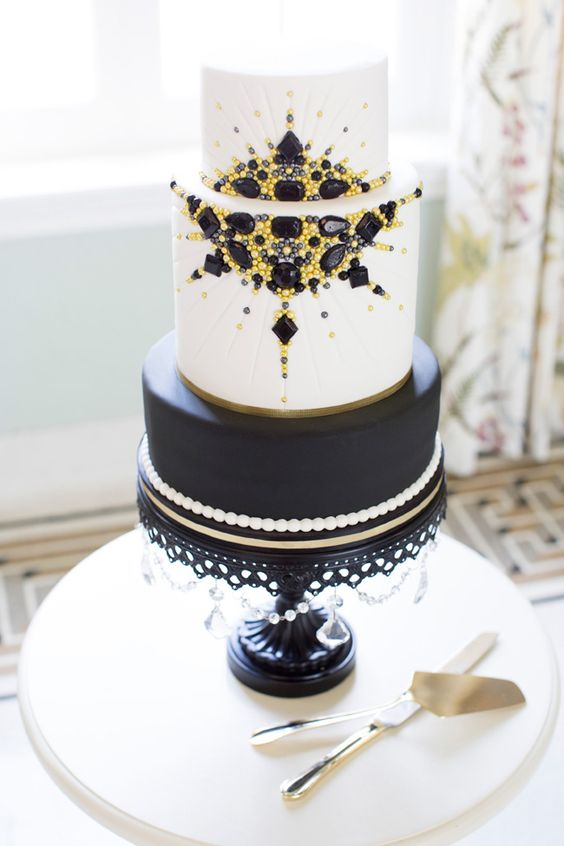 a black and white wedding cake with pearls, yellow and black beads and rhinestones
