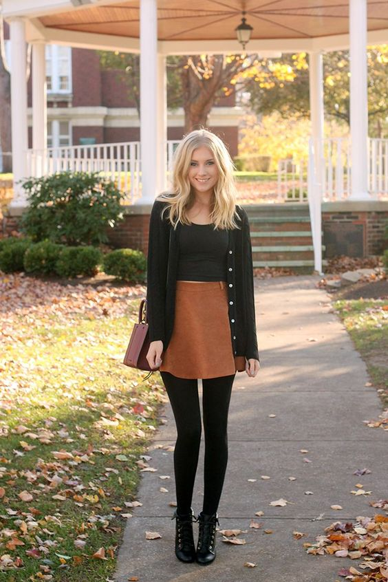 a fall outfit with a high waist orange skirt, a black crop top, a black cardigan, black tights and booties