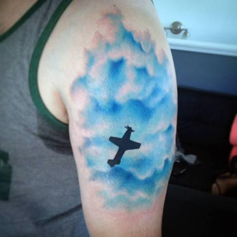 Blue clouds and plane tattoo on the hand