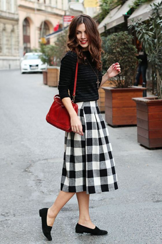 a striped black sweater, a plaid black and whiet skirt, black suede moccasins and a red bag