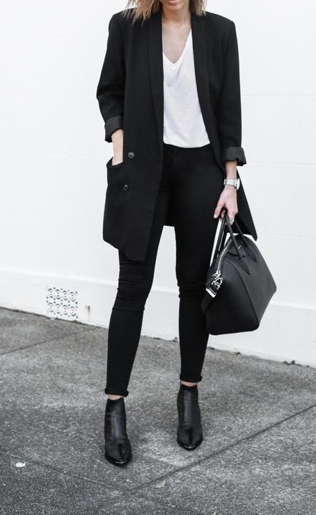 almost all-black work look with black jeans, a white oversized top, a black long blazer, black boots and a bag