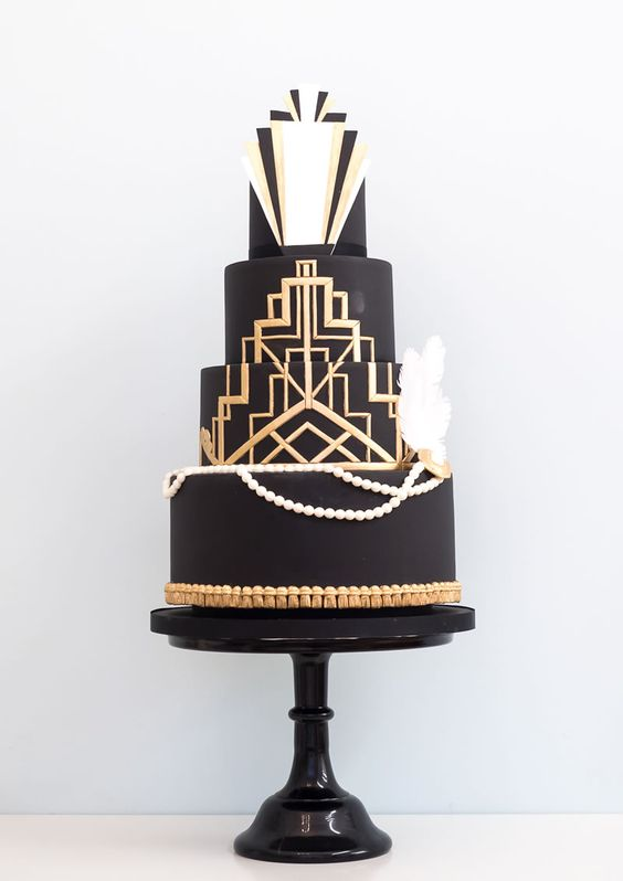 a chic black, gold and white wedding cake with gold geo decor, edible pearls and feathers