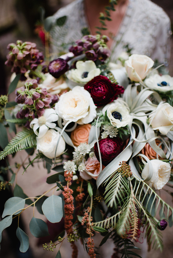 The bridal bouquet was lush, with textural greenery, neutrals and berry-hued blooms