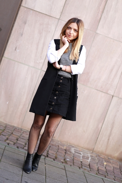 With gray shirt, black skirt, black ankle boots and cardigan