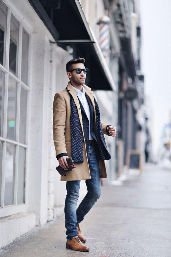 a layered fall look with jeans, a camel coat, a blazer and brown shoes