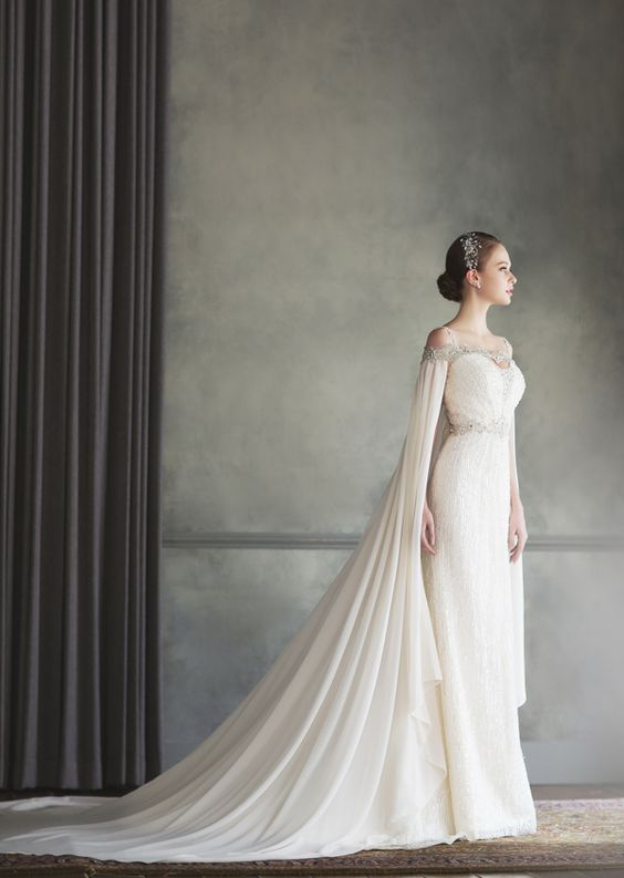a stylish jeweled cape perfectly fits the wedding dress detailing