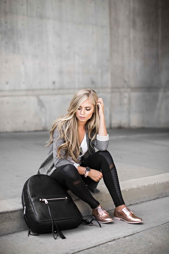 a grey blazer, a white shirt, black pants, metallic rose gold shoes and a black backpack
