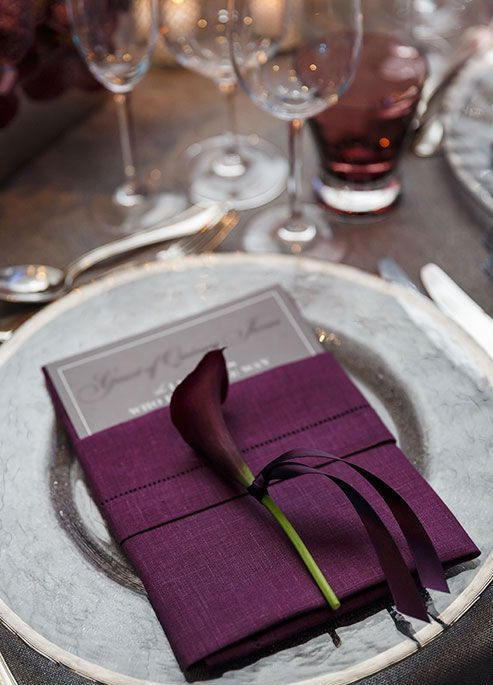 an elegant place setting with a purple napkin and a purple calle lily