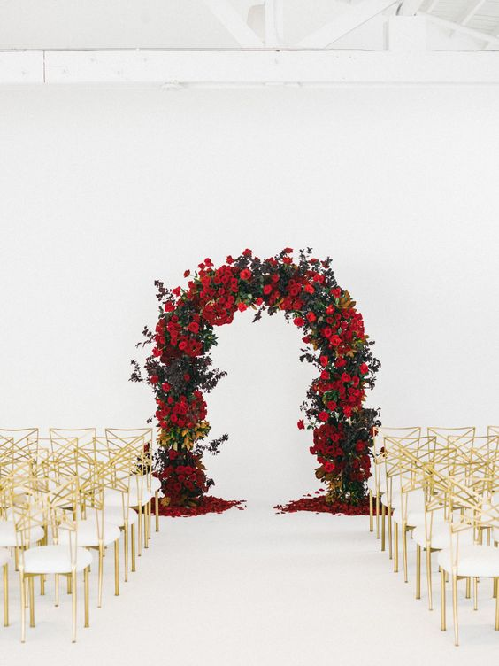 a lush red rose and greenery wedding arch with gold and white chairs make up a refined ceremony space