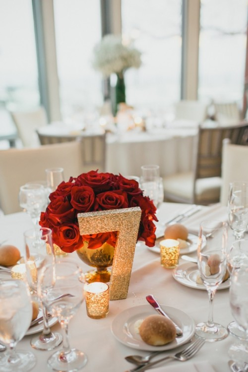a red roses canterpiece and a glitter table number and candle holders are a timeless idea