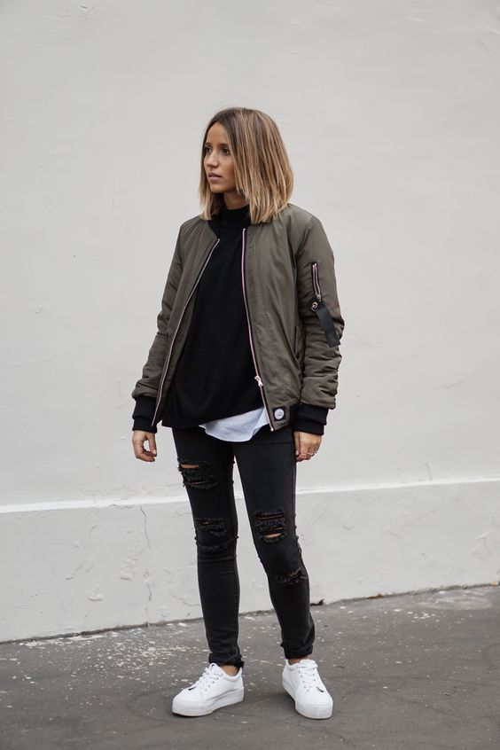 ripped black jeans, a black sweater, a white tee, white sneakers and an olve green bomber