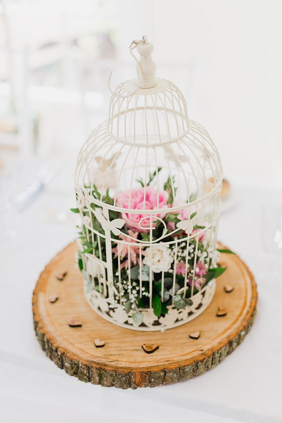 a white cage on a wooden slice with pink and white blooms inside for a rustic wedding