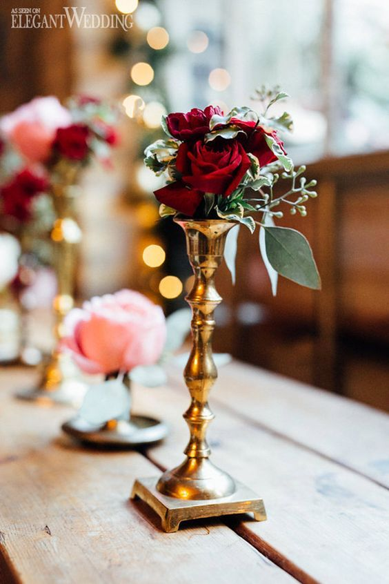 a gold candle holder with burgundy roses and greenery will be a nice decoration