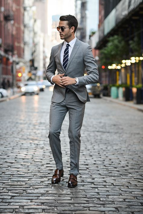 a grey suit, a striped tie and brown leather shoes for an elegant look