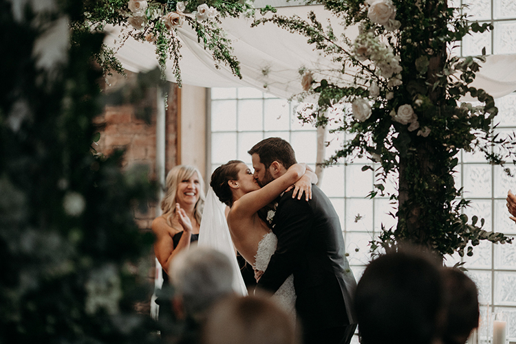 ceremony kiss - photo by Scarlet ONeill http://ruffledblog.com/industrial-space-meets-enchanted-forest-wedding