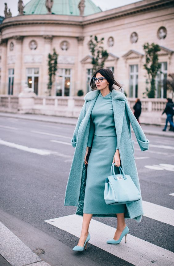 a grey suit with a top and a midi pencil skirt, a matching coat and blue shoes