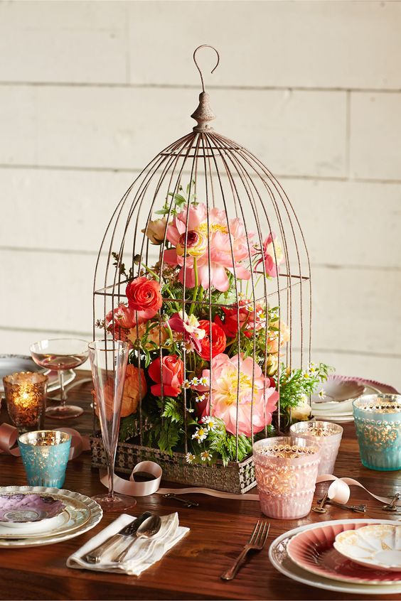 a vintage cage with lush red and pink blooms and greenery for a colorful wedding