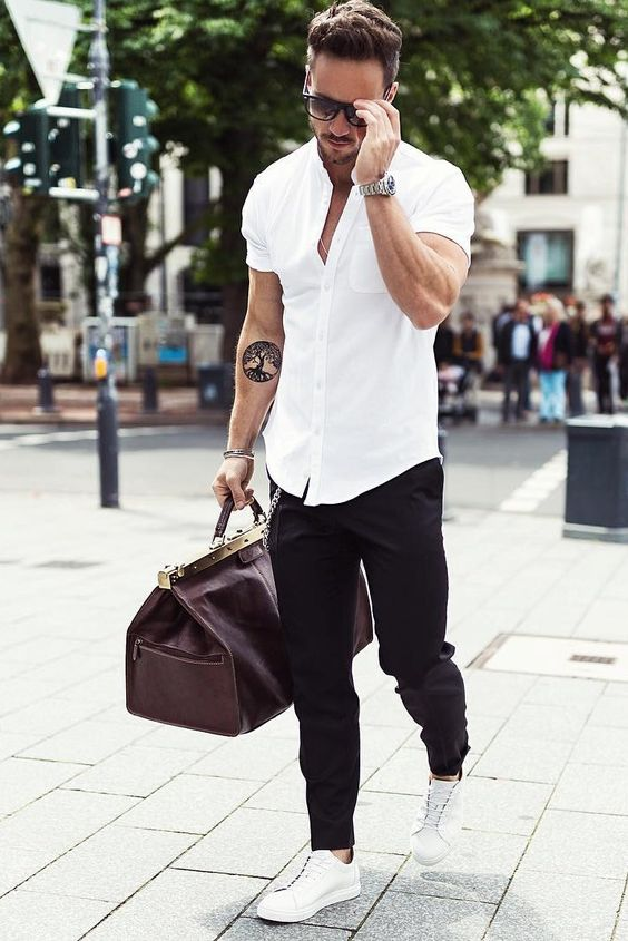 a white shirt with short sleeves, black pants, white chucks and a travel bag