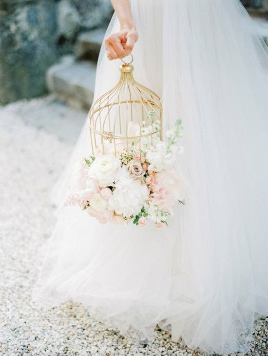 a gilded cage with lush white and blush blooms looks heavenly beautiful