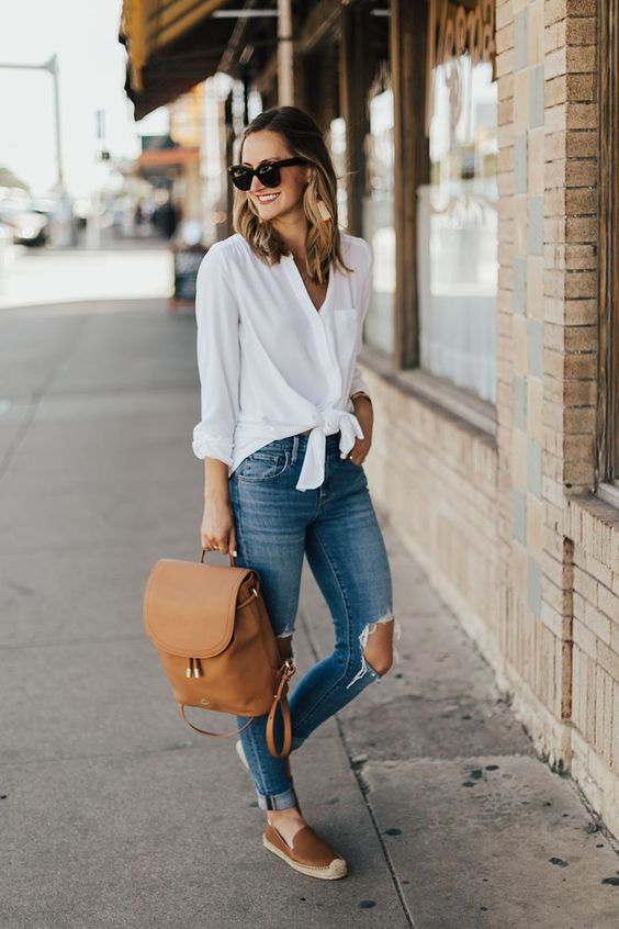 ripped jeans, a white shirt, brown slipons and a brown leather backpack in hand