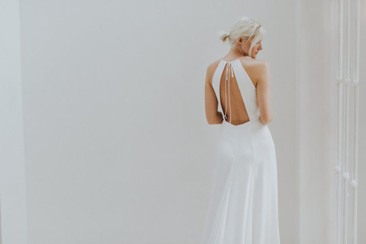 a modern wedding dress with a halter neckline and a cutout back on wide straps