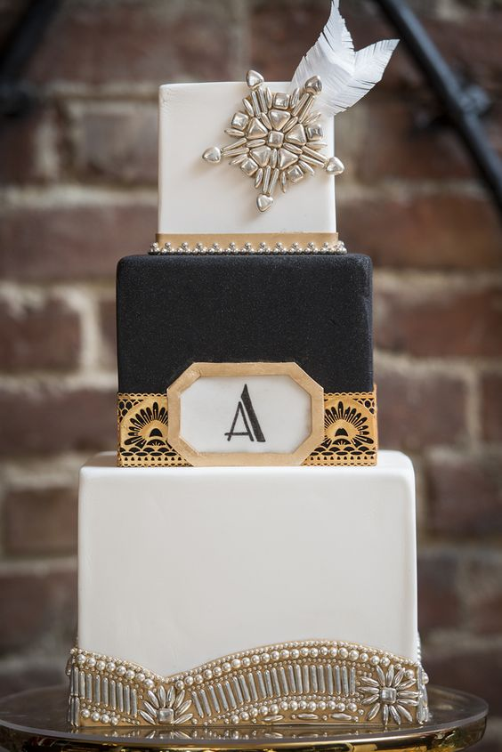 a gorgeous black and white square cake with gold geo decor, vintage brooches and beading and feathers