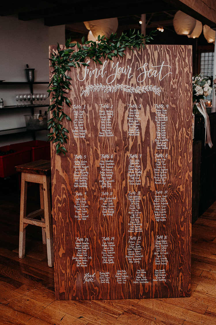 wooden seating charts with calligraphy - photo by Scarlet ONeill http://ruffledblog.com/industrial-space-meets-enchanted-forest-wedding