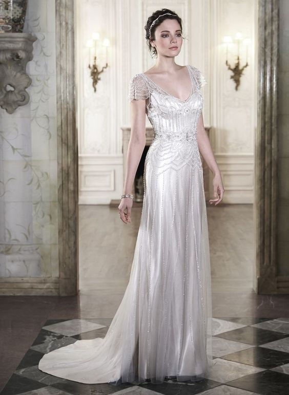 a sparkling art deco wedding dress with a deep V-neckline, cap sleeves, intricate beading and rhinestones