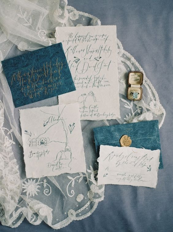 indigo envelopes with white invites and calligraphy, gold seals for a chic touch