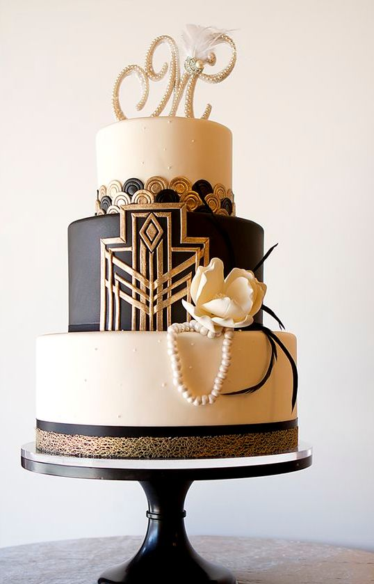 a black, white and gold wedding cake with geo decor, buttons, edible pearls, a sugar flower and a rhinestone monogram