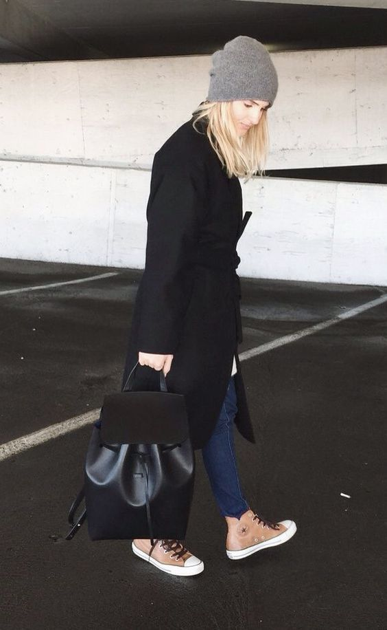 blue jeans, a black coat, high sneakers and a black leather and suede backpack