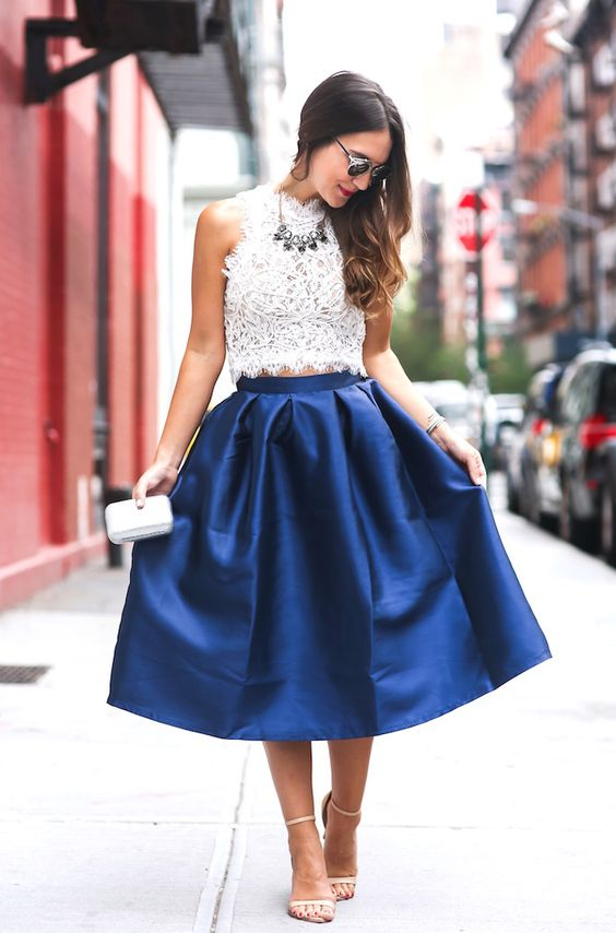 a sleeveless lace crop top, a statement necklace, a cobalt blue midi skirt, nude shoes