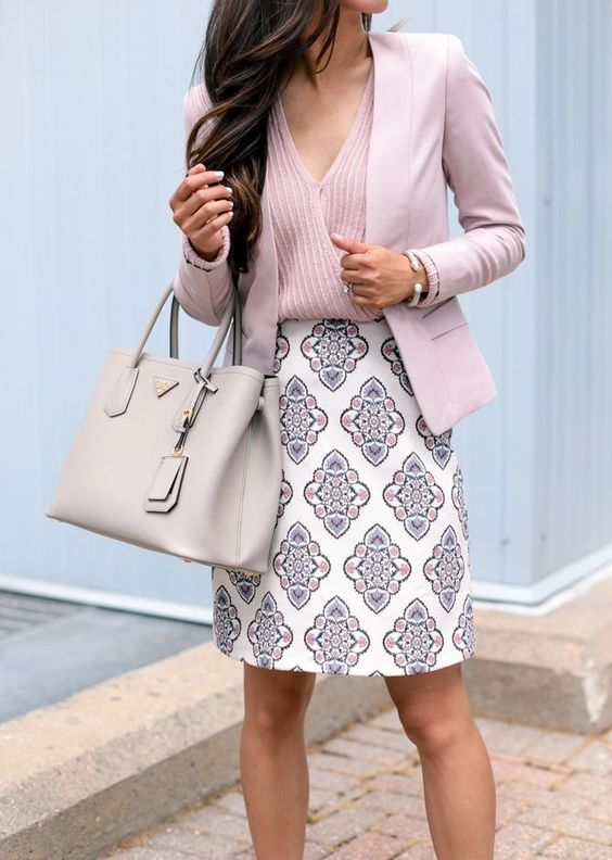 a pink striped top, a pink jacket, a printed knee skirt in pastel shades and a neutral bag