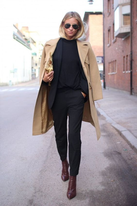a black suit with a black top, burgundy booties and a camel coat