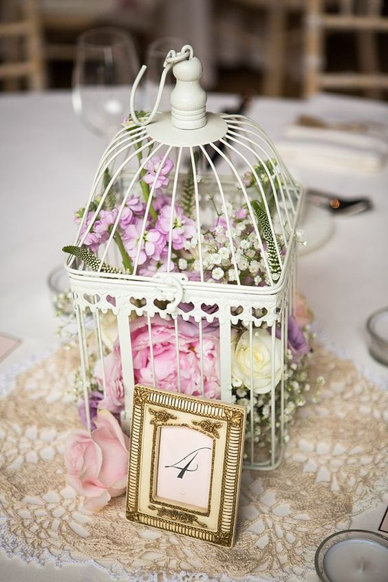 a white cage with lush florals of white, pink and lilac color for a sweet vintage wedding