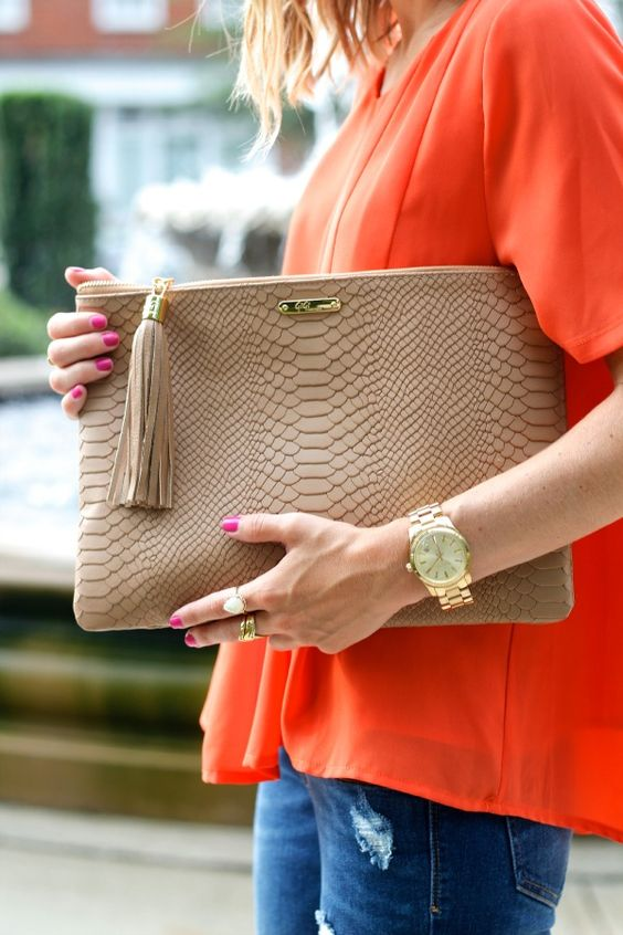 snake texture beige leather clutch with a tassel will fit many looks