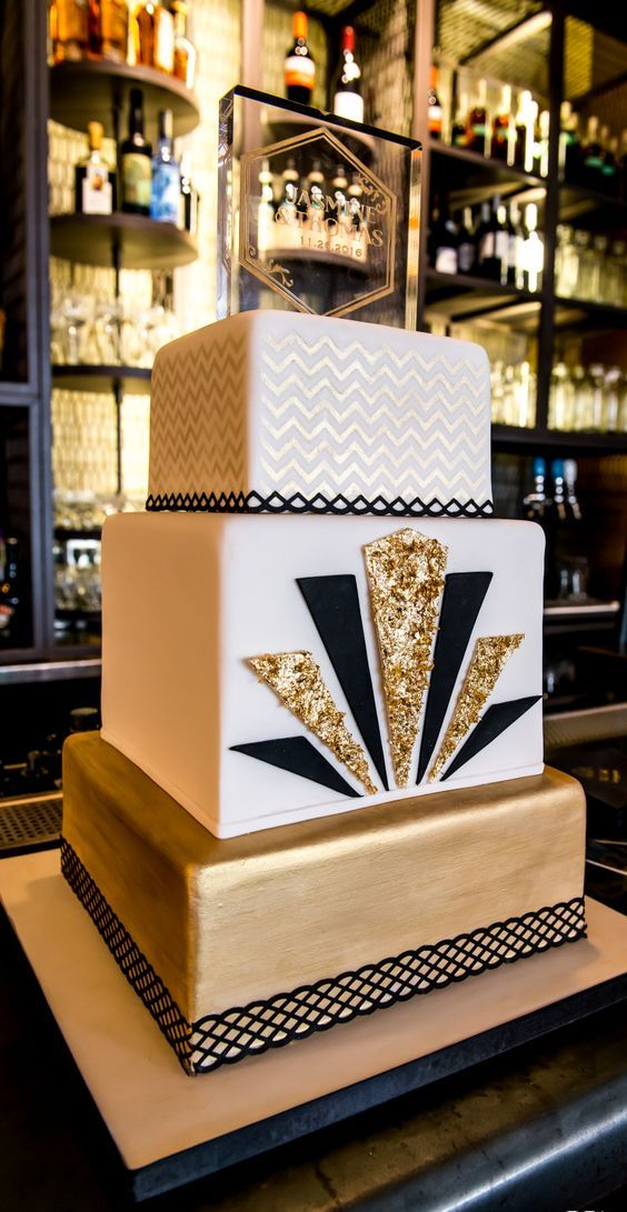 a chic square cake with a gold layer, a white layer decorated with black and gold glitter triangles and a gold and white chevron layer