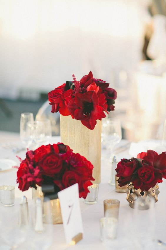 hot red blooms in gold vases with black ribbon for a chic wedding table setting