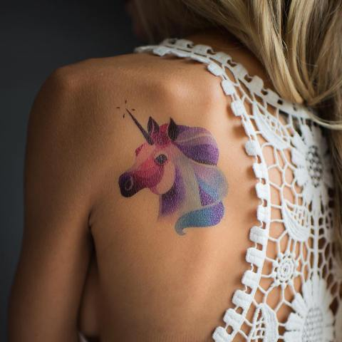 Pastel colored unicorn tattoo on the back